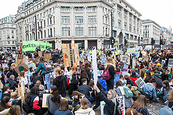London, UK. 12th April 2019. Students occupy Oxford Circus during the third Youth Strike 4 Climate. After gathering in Parliament Square, students marched through central London. The strike was organised by UK Student Climate Network and the UK Youth Climate Coalition to demand that the Government declare a climate emergency and take positive steps to address the climate crisis.
