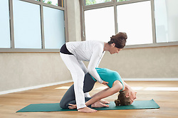 Yoga trainer helping young woman exercise