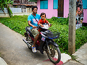 02 AUGUST 2018 - PAK KRET, NONTHABURI, THAILAND: A man and his child on a motorcycle on Ko Kret. There are no cars on the island, just motorcycles and bicycles. Ko Kret (also spelled Koh Kret) is a small island in the Chao Phraya River in Nonthaburi province north of Bangkok. It is about 2 km long and 1 km wide. It has seven main villages, the largest and most populous being Ban Mon. Ko Kret was created in 1722 when a canal was dug in the Chao Phraya River to bypass a bend. Most of the people on the island are ethnically Mon, from the hills of western Thailand and eastern Myanmar (Burma). The island is popular as a weekend daytrip from Bangkok. The island is famous for the Mon style pottery made on the island.      PHOTO BY JACK KURTZ