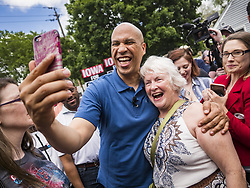 May 27, 2019 - Urbandale, Iowa, U.S - US Senator CORY BOOKER (D-NJ) takes selfies with people who came to a Memorial Day barbecue at his Iowa campaign headquarters. Sen. Booker is running to be the Democratic nominee for the US Presidency. Iowa traditionally hosts the the first selection event of the presidential election cycle. The Iowa Caucuses will be on Feb. 3, 2020. (Credit Image: © Jack Kurtz/ZUMA Wire)