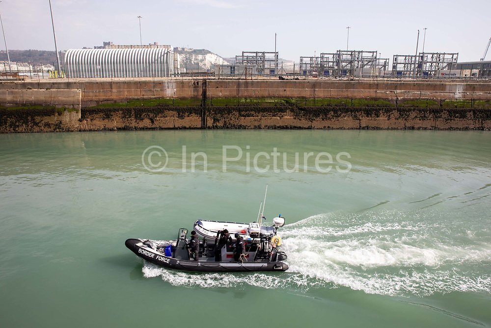 Boarder Force officer tow in an RIB Rigid Inflatable Boat into Dover after migrants were picked up by Boarder Force in the English Channel while crossing in their small inflatable dinghy on the 31st of March 2021 in Dover, Kent, United Kingdom. About 30 men, women arrived today on two small boats they were taken off the boat by UK Boarder Force officers and taken into a processing centre on the dock side.