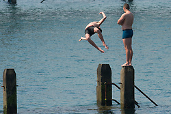 © Licensed to London News Pictures. 12/05/2016. Aberystwyth, Wales, UK. People at the seaside in Aberystwyth enjoying swimming and diving into the sea on the  last day of warm weather in the current mini-heatwave.  The temperatures are set to fall over the coming days, with bright but colder conditions prevailing over the country .  Photo credit: Keith Morris/LNP