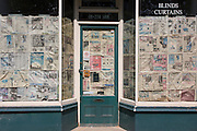 Newspaper obscuring the windows and doorway of a closed shop business in south London.