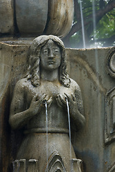 Statue of woman with water coming out of breasts in fountain of Parque Central, Antigua, Guatemala