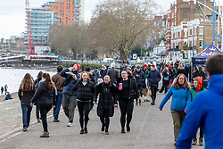 © Licensed to London News Pictures. 17/01/2021. London, UK. Members of the public enjoy a stroll past coffee and takeaway food stalls along a busy stretch of the Thames at Putney, South West London today as the government plead with the public to stay at home as much as possible. Today, Foreign Minister Dominic Rabb said that lockdown could be lifted in March but with tier systems in place as health chefs reveal that a 24/7 vaccination pilot will begin next week as total Covid-19 deaths reach over 88,000 this weekend. Photo credit: Alex Lentati/LNP