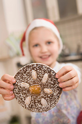 Girl showing gingerbread cookie, smiling, portrait