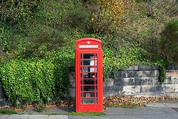 A single original old red telephone box.