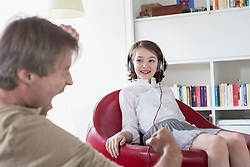 Daughter sitting on chair with headset while father singing