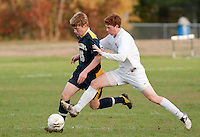Hopkinton's Billy French tries to get a foot on the ball from behind Bow's Jason Underhill as they charge down field during Monday afternoon's NHIAA DIvision III soccer matchup at Hopkinton High School.  (Karen Bobotas/for the Concord Monitor)