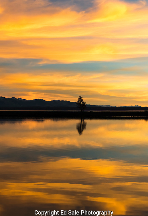 Reds, yellows, and blues paint the sky and clouds and reflect in the water of Lake Yellowstone during an autumn sunset.