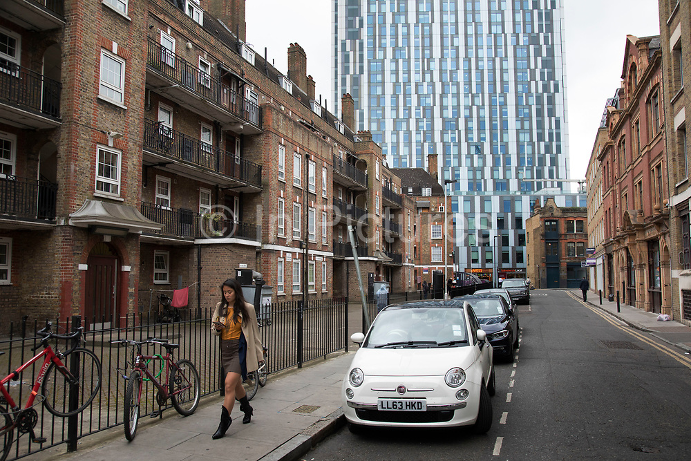 Social housing stands alongside a modern corporate tower in the City of London, England, United Kingdom. Old and new architecture for different uses.