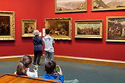 Art lovers appreciate paintings in the Scottish National Gallery on The Mound in Edinburgh, on 25th June 2019, in Edinburgh, Scotland. The Scottish National Gallery displays some of the greatest art in the world, including masterpieces by Botticelli, Raphael, Titian, Rembrandt, Vermeer, Constable, Turner, Monet, Van Gogh and Gauguin, amongst many others.