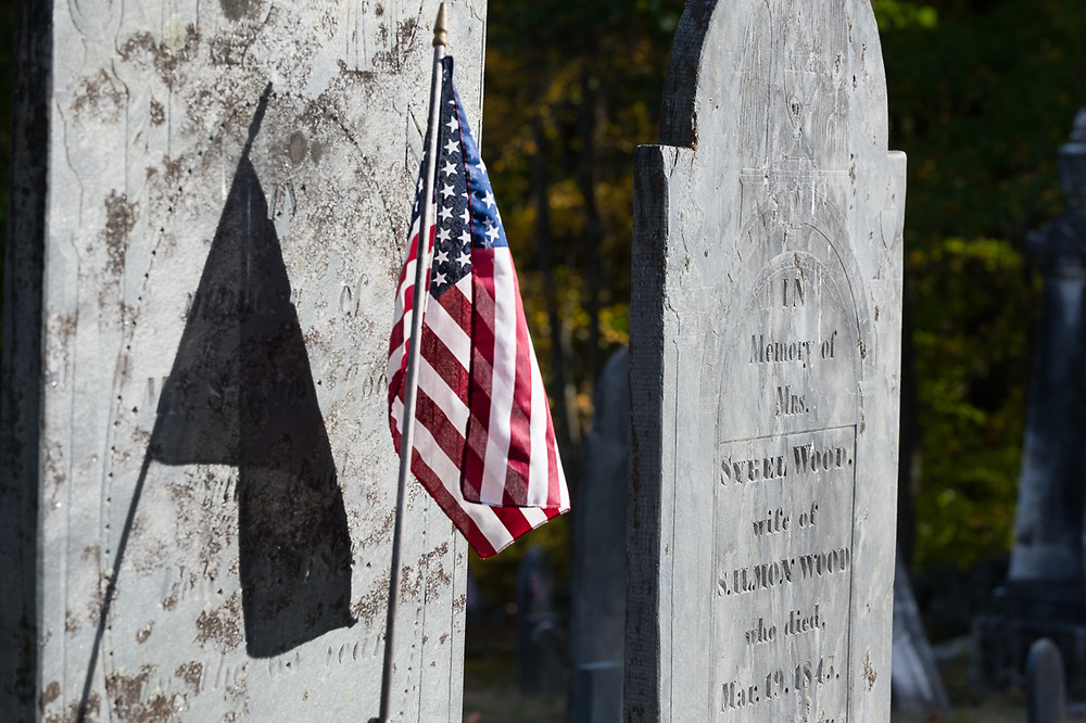 American flag and old cemetery headstone,  afternoon light, October, Hillsborough County, Hancock, New Hamphshire, USA