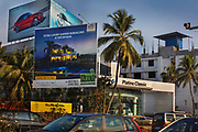 Advertisements for luxury villas overlook a BMW car showroom on 28th February 2018 in Ernākulam, Kerala, India. The wealth in the Kerala state has become inflated by the many men who work in the Gulf countries and bring their earnings home.