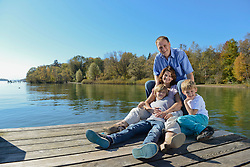 Family sitting on boardwalk, smiling, Bavaria, Germany