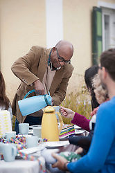 Black man serving coffee at family party, Bavaria, Germany