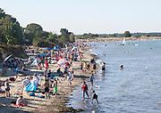 Late afternoon crowded summer sandy beach, Studland Bay, Swanage, Dorset, England, UK