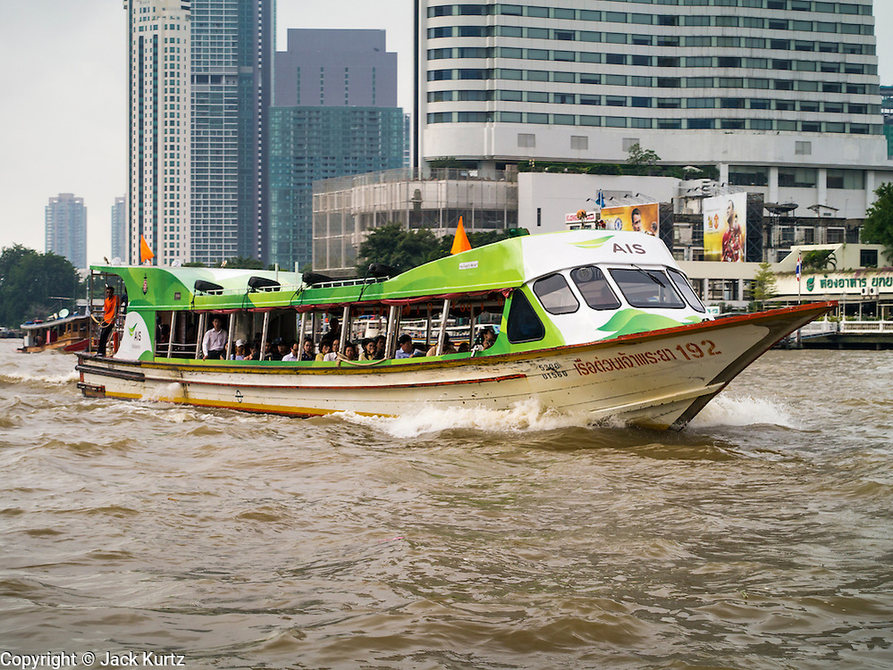 09 OCTOBER 2012 - BANGKOK, THAILAND: A Chao Phraya Express Boat goes up the Chao Phraya river past the Bangkok skyscrapers headed to the northern suburbs. The Chao Phraya Express Boats run through Bangkok from its northern suburbs to just south of the city. Boats and ships play an important in daily life in Bangkok. Thousands of people commute to work daily on the Chao Phraya Express Boats and fast boats that ply Khlong Saen Saeb. Boats are used to haul commodities through the city to deep water ports for export.              PHOTO BY JACK KURTZ
