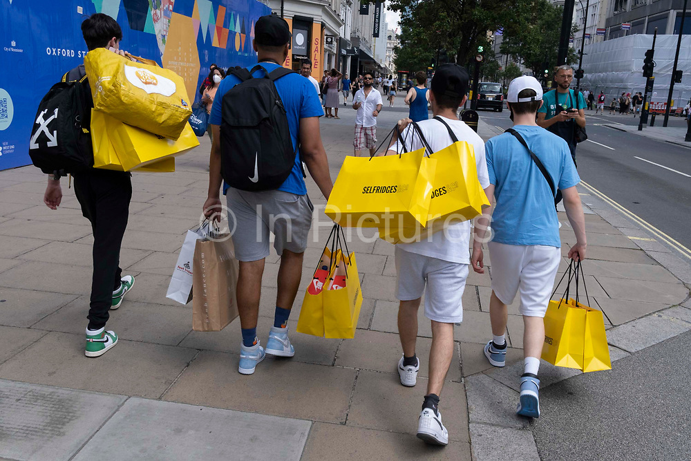 Young Men carry their yellow Selfridges shopping bags purchases on Oxford Street in the West End on Covid Freedom Day. This date is what Prime Minister Boris Johnsons UK government has set as the end of strict Covid pandemic social distancing conditions with the end of mandatory face coverings in shops and public transport, on 19th July 2021, in London, England.
