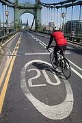 After being closed indefinitely to all traffic due to structural faults, a cyclist pedals over the 20mph across Hammersmith Bridge, on 11th April 2019, in west London, England. Safety checks revealed critical faults and Hammersmith and Fulham Council has said its ben left with no choice but to shut the bridge until refurbishment costs could be met. The government has said that between 2015 and 2021 its is providing £11bn of support to the 132-year-old bridge.