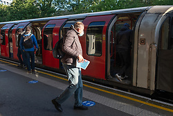 © Licensed to London News Pictures. 14/05/2020. London, UK. A commuter at Hanger Lane tube station boards a train during morning rush hour. The government relaxed some rules allowing people to travel to work if they are unable to work from home. Photo credit: London News Pictures