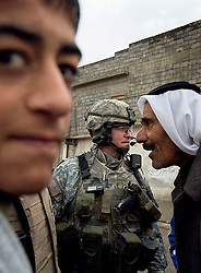 Maj. Jonathan Fox, an officer with the 1st Infantry, 17th Regiment, talks with locals while patrolling in western Mosul, Iraq, Dec. 16, 2005.<br />This is part of an effort to provide security in preparation for Iraq's first post-Saddam parliamentary elections. The western sector is home to Mosul's primarily Sunni population, which has been resistant to the American presence in Iraq.