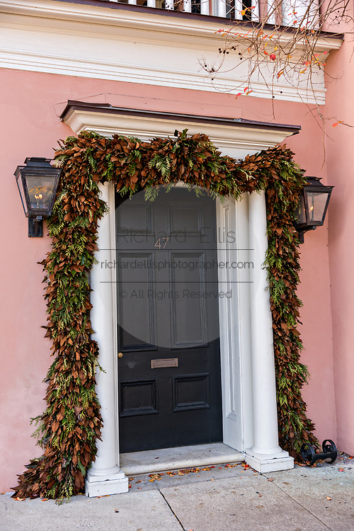 Traditional low country style magnolia leaf Christmas roping decorates a historic home along the Battery in Charleston, SC.