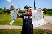 """24 JULY 2020 - DES MOINES, IOWA: RYAN BARCUS, a special education teacher from Ankeny, IA, stands on the grounds of the State Capitol and cheers teachers driving around the capitol. Hundreds of teachers from across Iowa came to the state capitol Friday to protest Governor Kim Reynolds' order that school must reopen with in person education and minimized the potential for """"distance learning."""" The event was one of the largest COVID-19 protests in Iowa since the pandemic started, more than 740 teachers signed up to attend the protest. After the protest officially ended, many teachers left the capitol and drove to Gov. Reynolds' residence, where they drove around her mansion and honked horns. Some people left notes on the entrance to the governor's residence. Gov. Reynolds ordered the school reopening last week, but according to teachers, the state has not implemented health guidelines or bought protective equipment like face masks in the quantity required to slow the spread of the Coronavirus (SARS-CoV-2). Iowa's numbers of COVID-19 infections are up statewide.         PHOTO BY JACK KURTZ"""