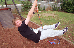 Young boy playing on rope swing in adventure playground,