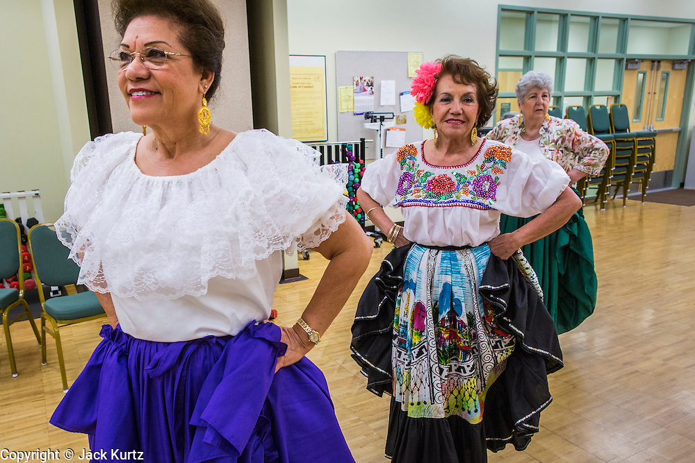27 JUNE 2012 - GLENDALE, AZ:  MARGIE MAY, 65 years old, left, SHENY RUIZ MILLIGAN, 67, and HELENA ROER, 75, dance during rehearsal for the Senior Fiesta Dancers at the Glendale Adult Center, in Glendale, AZ, a suburb of Phoenix. Dancing as a part of workout regimen is not unusual, but the Senior Fiesta Dancers use Mexican style folklorico dances for their workouts. The Senior Fiesta Dancers have been performing together for 15 years. They get together every week for rehearsals and perform at nursing homes and retirement centers in the Phoenix area once a month or so. Their energetic Mexican folklorico dances keep them limber and provide a cardio workout.   PHOTO BY JACK KURTZ