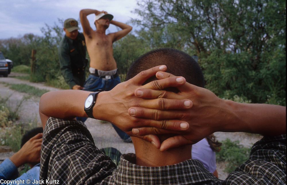 27 JULY 2001 - NACO, ARIZONA, USA: Butch Gamboa, a 5 1/2 year veteran of the US Border Patrol, searches a member of a group of undocumented immigrants he caught trying to enter US illegally near Naco, AZ, July 27, 2001. Undocumented immigration from Mexico through southeastern Arizona has gone down by more than 40 percent in 2001 because of increased Border Patrol activity along the Arizona/Mexico border. .PHOTO BY JACK KURTZ .NMR