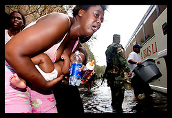 1st Sept, 2005. Mass evacuation of New Orleans begins. A mother comes close to collapsing as she approaches the first bus leaving New Orleans.