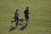 In the third week of the UK government's lockdown during the Coronavirus pandemic, when the daily UK death rate rose by another 761 to 12,868 and with nearly 100,000 reported cases. two Londoners run alongside their dog take their daily exercises in Ruskin Park, a public green space in the south London borough of Lambeth, on 15th April 2020, on 15th April 2020, in London, England.