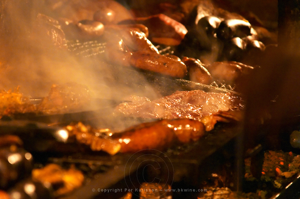 The restaurant kitchen with a big grill barbecue where all sorts of pork beef and chicken meat and sausages are grilled. Close-up of some sausages and meat pieces on the grill. at the restaurant La Estacada on the waterside Montevideo, Uruguay, South America