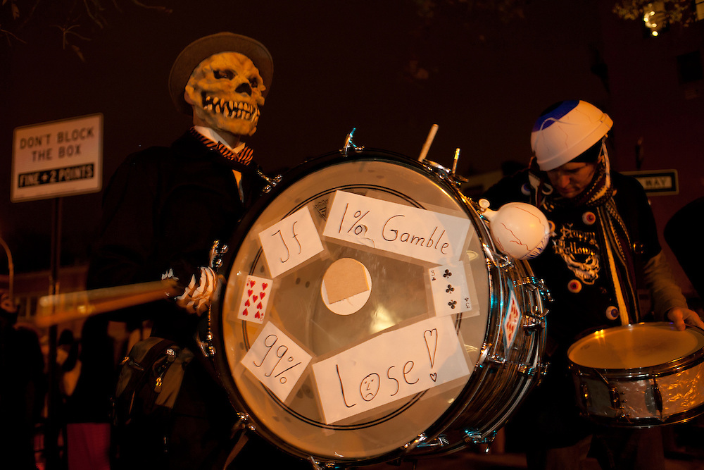 A drummer in skeleton costume, with Occupy Wall Street signs on his drum.
