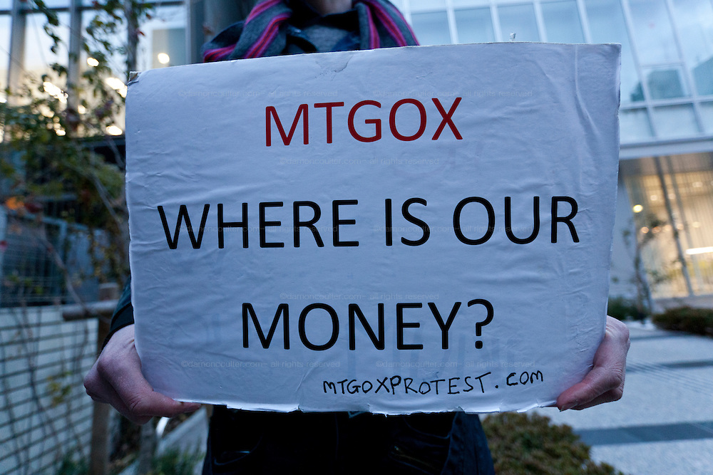 """Bitcoin trader, Kolin Burges, from the United Kingdom, holds a sign asking """"Mt Gox, Where is our money?"""" as he protests in front of the abandoned offices of Tokyo-based Bitcoin exchange, Mt. Gox. Shibuya, Tokyo, Japan. Friday February 28th 2014. Mr Burges flew to Japan to personally confront the trading company over his inabilty to withdraw over 260,000 USD worth of the electronic currency. Mt. Gox officially filed for bankruptcy protection on February 28th 2014"""