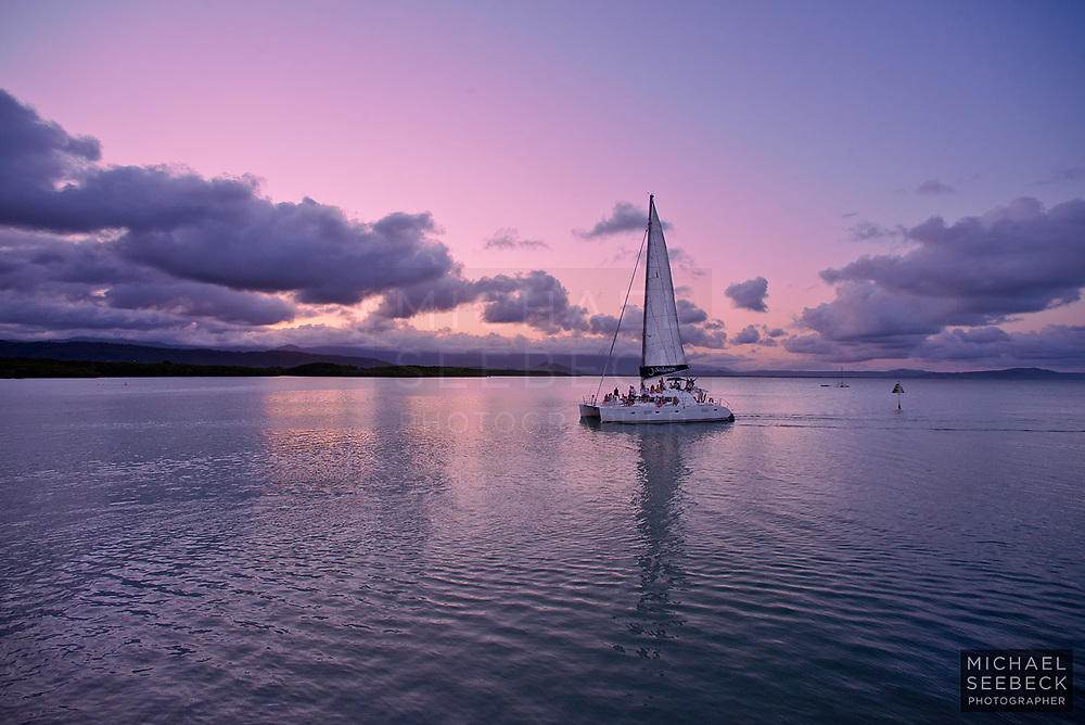 A sunset sail catamaran returns to harbour at Port Douglas just after sunset.<br /> <br /> Open Edition Print / Stock Image