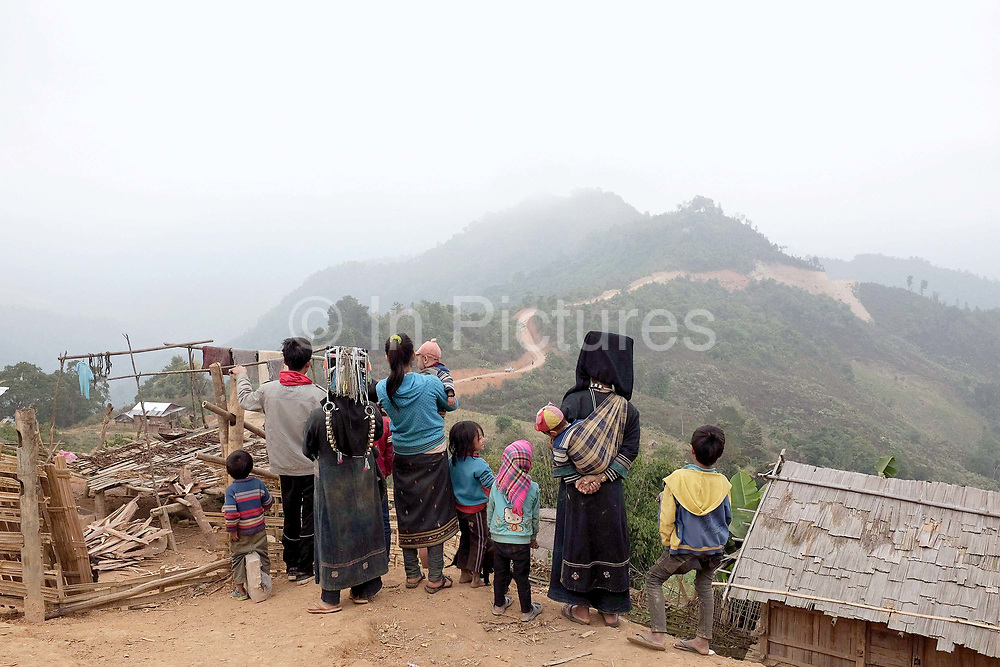 Villagers in the remote Akha Nuquie village of Ban Chakhampa watch construction traffic drive along the new road, Phongsaly province, Lao PDR. Whilst not affected directly by the Nam Ou Cascade Hydropower Dam 6 construction project, the village of Ban Chakhampa has benefitted from the new road passing by on the way to Ban Watai, a village which has recently been relocated due to the dam construction.