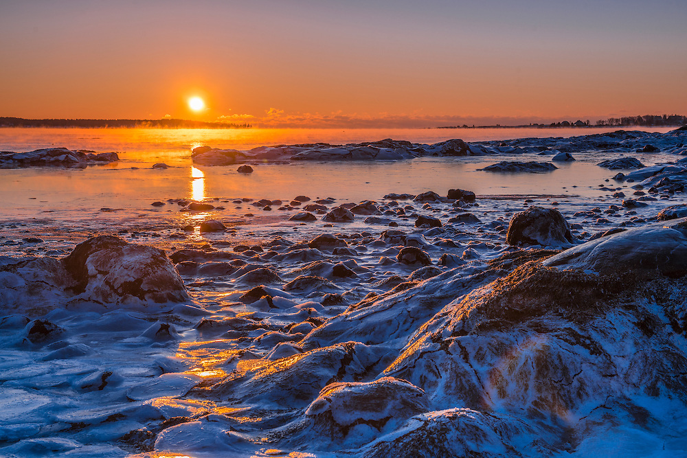 Winter sunrise over ice coated rocks and harbor, Acadia National Park, Thompson Island, ME