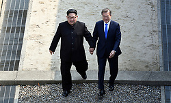 April 27, 2018 - Panmunjom, Korea - North Korean leader Kim Jong Un, left, and South Korean President Moon Jae-in cross the military demarcation line at the border village of Panmunjom in Demilitarized Zone. Their discussions will be expected to focus on whether the North can be persuaded to give up its nuclear bombs. (Credit Image: © Prensa Internacional via ZUMA Wire)