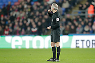 Martin Atkinson blows his whistle after initially giving a yellow card, he received information via the VAR referee informing him to send off Grimsby Town defender Andrew Fox (19) during the The FA Cup 3rd round match between Crystal Palace and Grimsby Town FC at Selhurst Park, London, England on 5 January 2019.