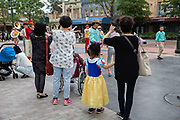 A girl wearing a Snow White dress looks at a passing marching band at Walt Disney Co.s Shanghai Disneyland theme park  towards the iconic castle during a trial run ahead of its official opening, in Shanghai, China, on Wednesday, June 8, 2016. The $5.5 billion Shanghai Disneyland is one  of the most profitable Disney ventures in the world and the first theme park on mainland China.