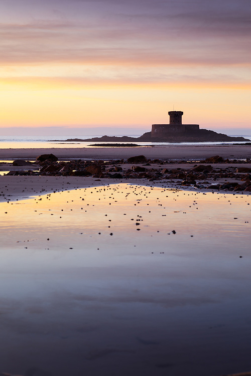 Purple and orange sky reflecting in pools of water in the sand in front of La Rocco Tower at St Ouen's Bay in Jersey, Channel Islands