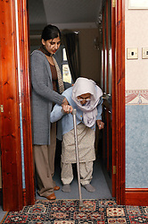 Granddaughter helping her Sikh elderly grandmother to walk through a doorway,