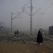 Migrants and refugees wander around the train tracks at the Greek-Macedonian border station of Idomeni, Greece. Around 13,000 migrants and refugees, mostly from the Middle East and African nations, are believe to be stranded here awaiting a chance to proceed their journey towards Germany and other northern European countries.