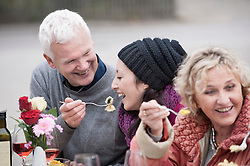 Father feeding pasta his daughter on dining table in backyard and smiling, Bavaria, Germany