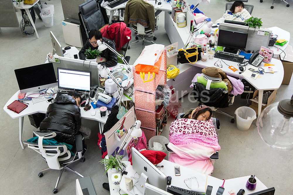 Employees take naps during lunch hour at the Wechat division of Tencent, photographed in Guangzhou, China on 24 December 2013. Wechat is quickly becoming China's favorite social media tool and have already started to erode the income of internet giants such as Sina's Weibo as well as telecommunication state monopolies like China Mobile and China Unicom.