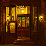 About the Subject: A night time street scene in Vieux Montreal. <br /> <br /> About the Capture: Coach lamps cast a dappled pattern of shadows and light on a street corner in Old Montreal. The cheerful motif of the stained glass door contrasts with the goblin-like feeling on the outside with its stone walls and steps and amber light.