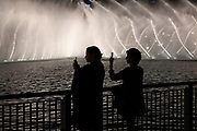 Two women photographing the famous Dubai Fountain water show with their IPhones. It is a choreographed fountain system located on the 30 acre manmade Burj Khalifa Lake.