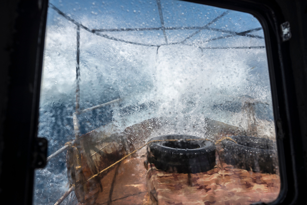 A boat in Papua New Guinea carrying about 30 people and a load of copra from Karkar Island to the town of Madang crashes through rough water on the Bismarck Sea.